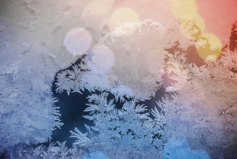 Frost on window. Glare through glass. Festive background with winter theme. bokeh blurred abstract colorful background stock photos