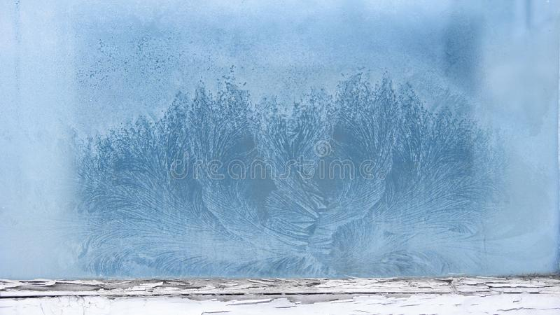 Frost pattern on the window in an old wooden frame. background of icy fairy tale house window stock images