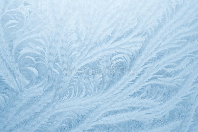 Frost patterns on window glass in winter season. Frosted Glass Texture. Blue background stock photo