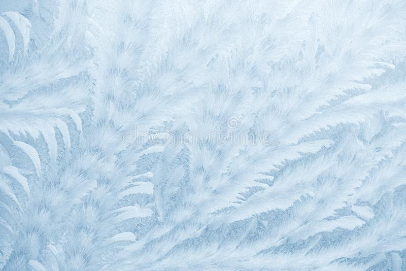 Frost patterns on window glass in winter season. Frosted Glass Texture. Blue background royalty free stock photography
