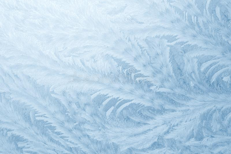 Frost patterns on window glass in winter season. Frosted Glass Texture. Blue background royalty free stock photo