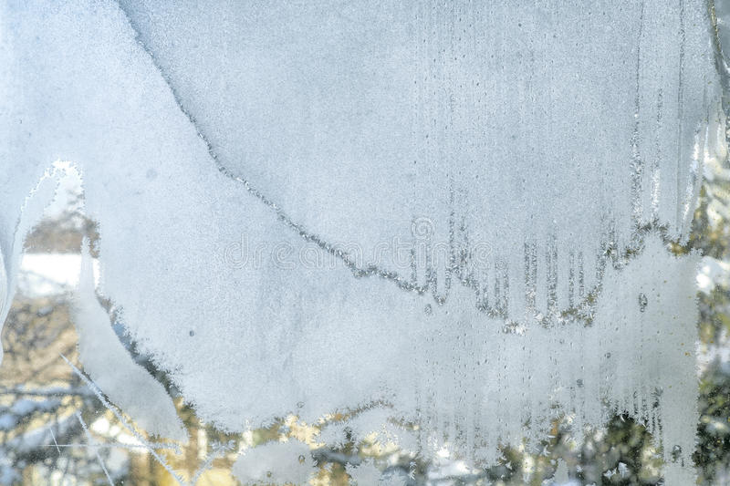 Frost. On a window with a nature scene in the back stock photography