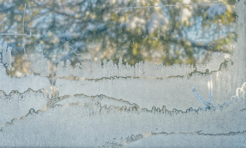 Frost. On a window with a nature scene in the back stock photo