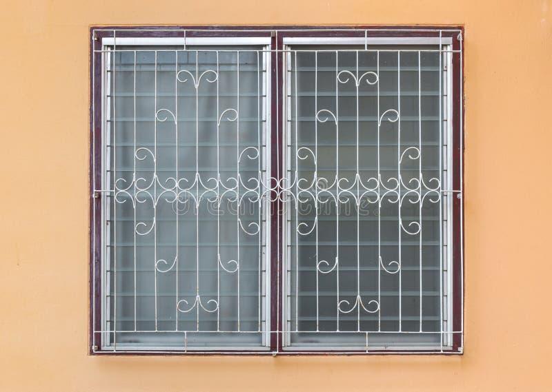 Frostad Glass luftventil Windows med krökt stål på den orange betongväggen arkivfoto