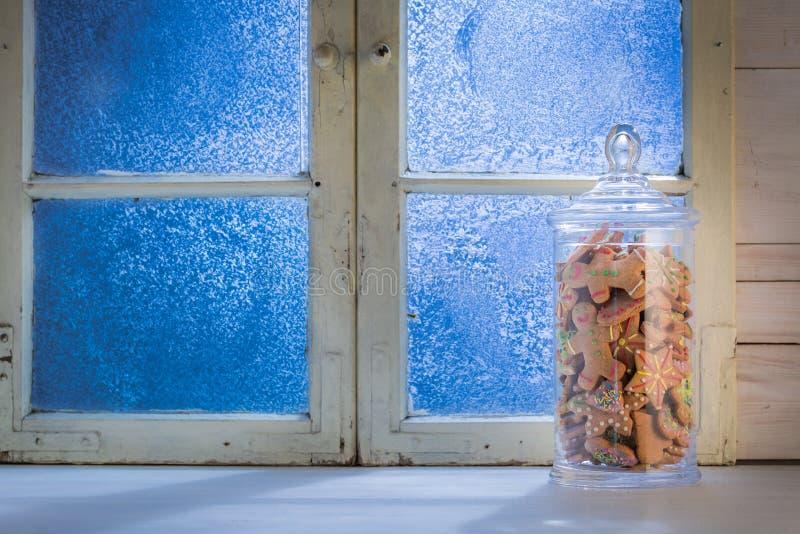 Frostat blått fönster med kakor i kruset för jul arkivbilder