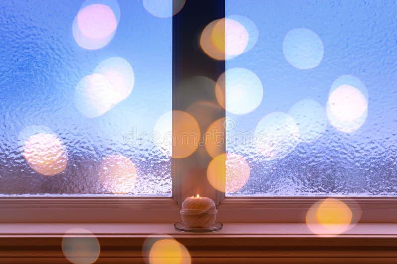 Frostat fönster, brännande stearinljus och bokehljus royaltyfria foton