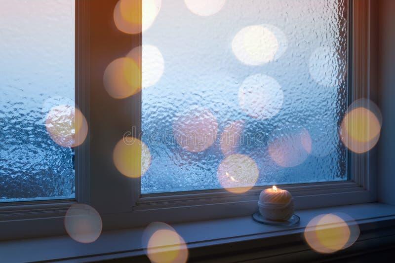 Frostat fönster, stearinljus och guld- bokehljus royaltyfria foton