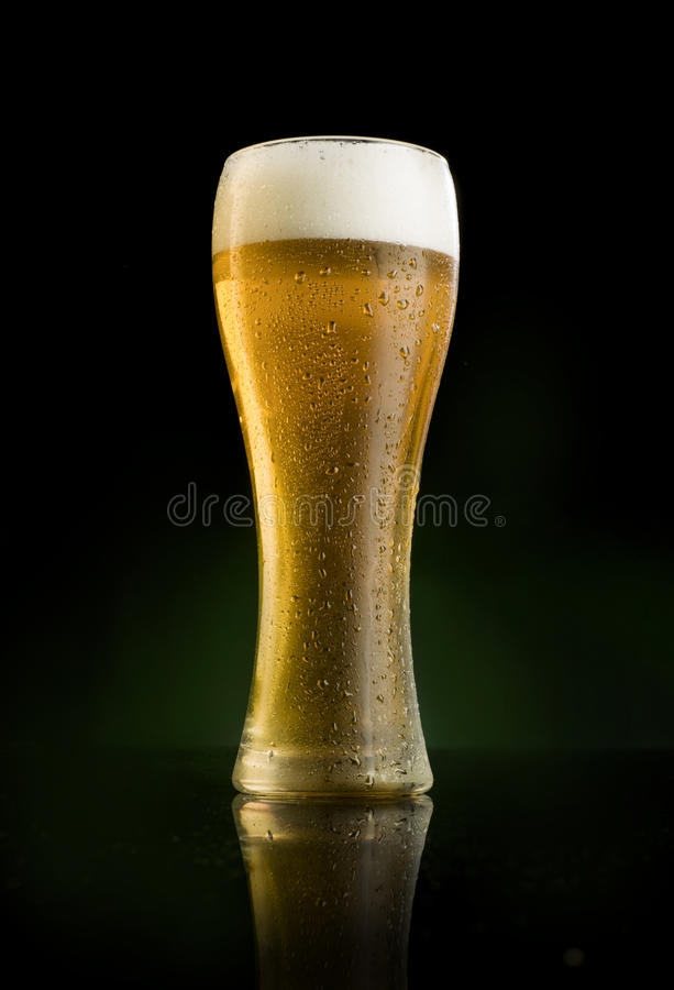 Frosted beer glass full. A frosted beer glass on dark background with water droplets stock photography