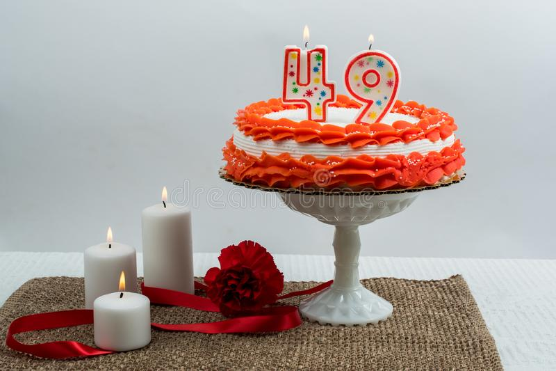 Frosted cake with 49 candle. Frosted cake on a cake stand with 49 candle on it. Candles, ribbon and a carnation scattered around the stand stock photography