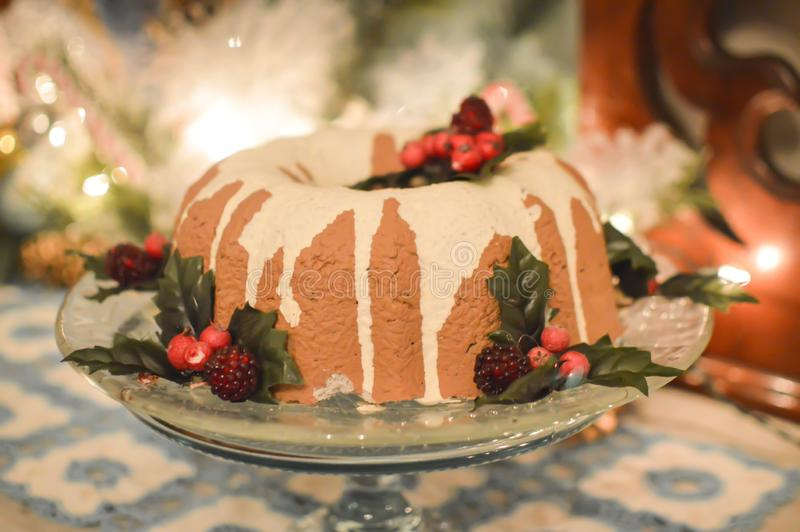 Frosted Holiday Bundt Cake on Platter. A frosted or glazed, holiday bundt cake with holly and berries and Christmas lights in background royalty free stock photo