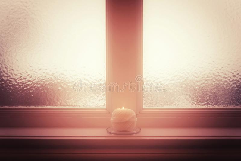 Frosted okno i płonąca świeczka w mglistym świetle i fotografia royalty free