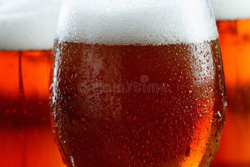 Frostiga exponeringsglas av kallt öl skummar, täckte med droppar, closeup arkivfoto