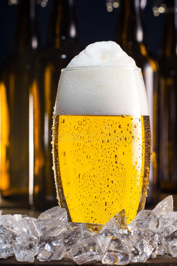 Frostigt exponeringsglas av öl med iskuber arkivbilder