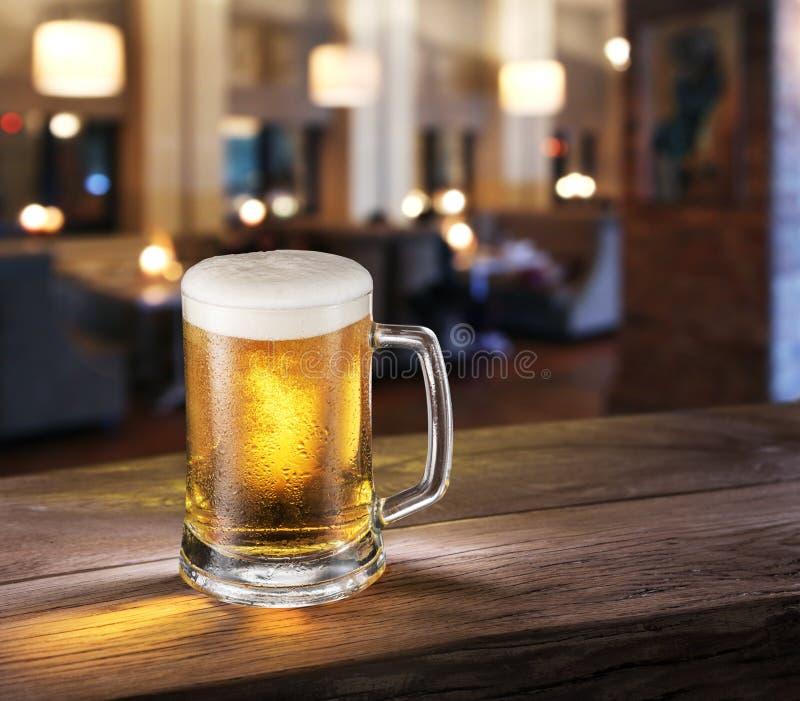 Frostigt exponeringsglas av ljust öl på stångräknaren royaltyfria foton