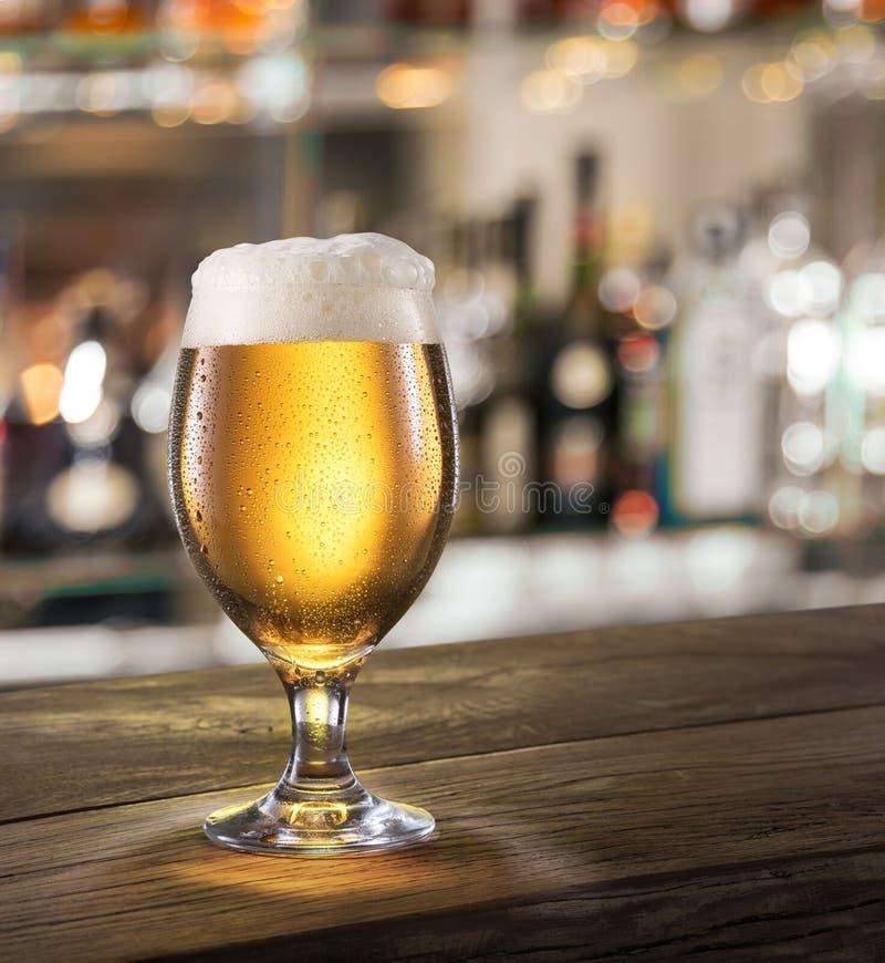 Frostigt exponeringsglas av ljust öl på stångräknaren arkivfoton