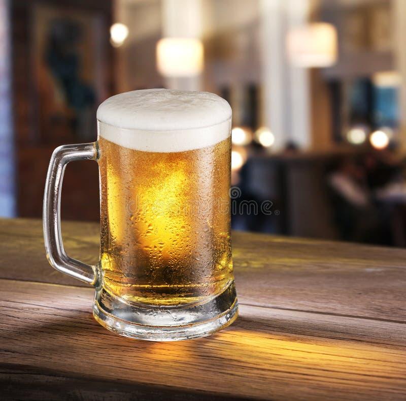 Frostigt exponeringsglas av ljust öl på stångräknaren royaltyfri fotografi