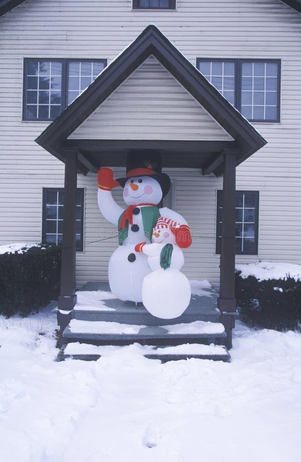 Frostigt snögubben efter insnöat nytt för vinter - ärmlös tröja under den främsta dörröppningen för julberöm av hemmet arkivfoton