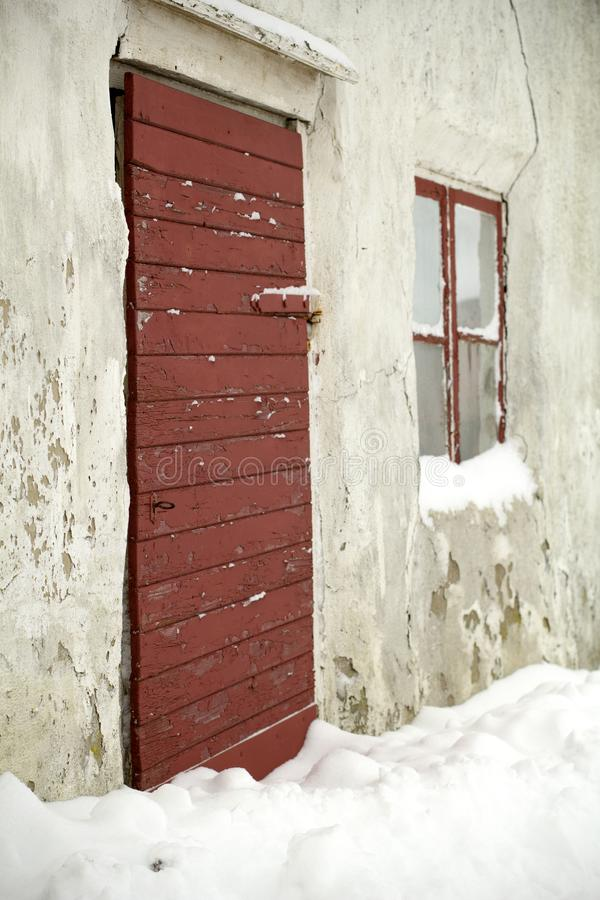 Frostigt vinterfönster och dörr som är insnöade arkivbild