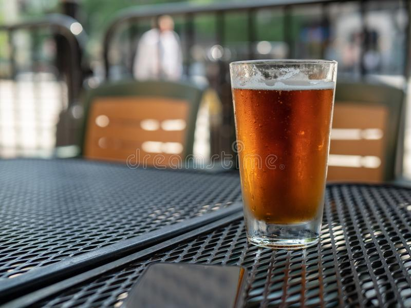 Frosty beer glass sitting on outdoor patio table stock photo