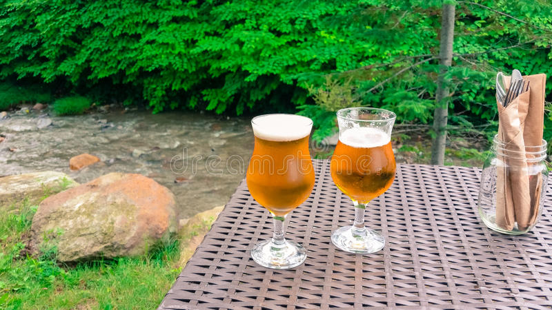 Frosty beer ready to sip by bubbling brook. Sitting by bubbling brook with frosty beers ready to sip while waiting for meal stock photo