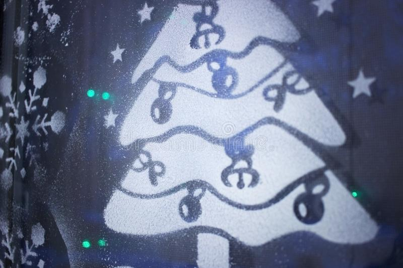 Frosty drawings on the window, frost, background with copy space, New Year. Christmas drawing on the window a Christmas tree stock photo