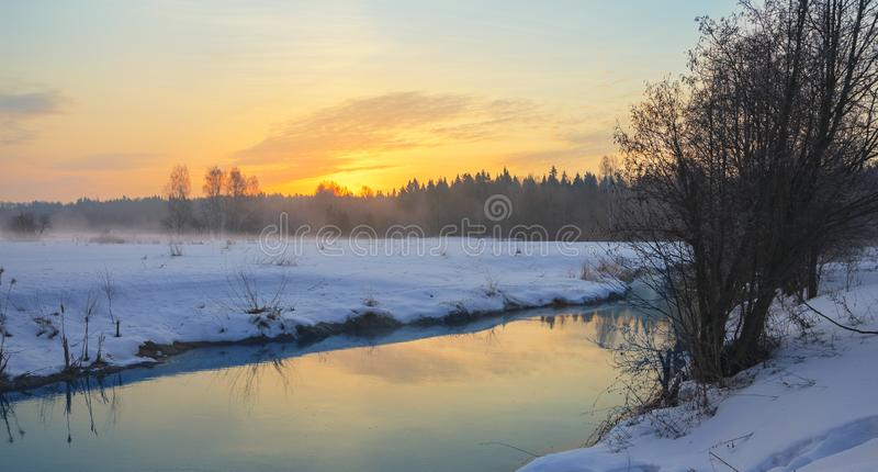 Frosty foggy winter landscape with small forest river and rising sun. Fog over the snow covered meadow in cold winter morning stock image