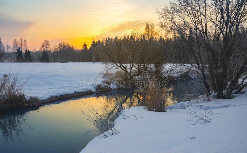 Frosty foggy winter landscape with small forest river and rising sun. Fog over the snow covered meadow in cold winter morning royalty free stock photography