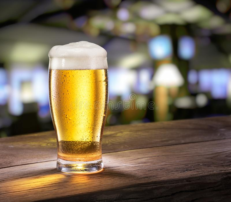 Frosty glass of light beer on the bar counter. royalty free stock photo