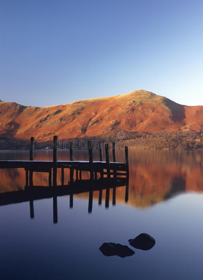 Frosty jetty, Derwentwater, Cumbria. A calm winters morning on the eastern side of Derwentwater, looking over to the summit of Cat bells mountain, frost covers royalty free stock photos