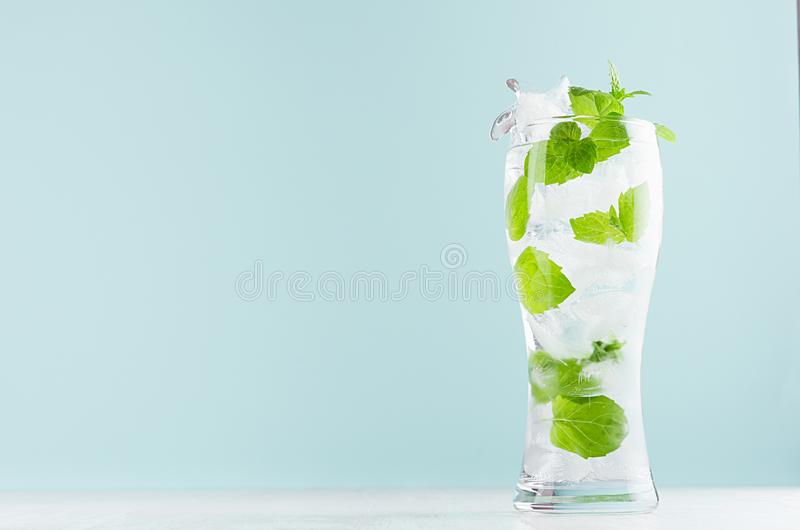 Frosty mint lemonade with green leaf, ice cubes and mineral water in elegant glass on white wood table, mint color wall. Frosty mint lemonade with green leaf royalty free stock images
