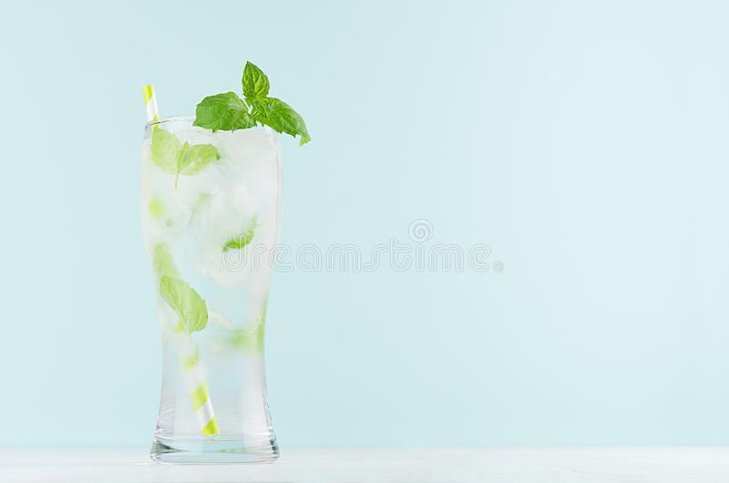 Frosty mint lemonade with green leaf, ice cubes, striped straw, mineral water in elegant glass on white wood table, mint color. Frosty mint lemonade with green stock image