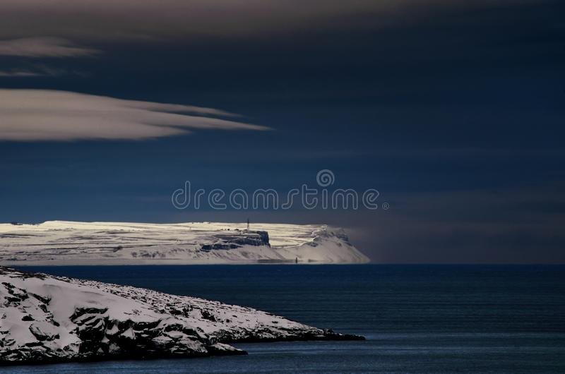 Frosty night landscape the Arctic Ocean. Northern severe cold nature cliffs. Dark deep blue water and sky, white clouds stock photos