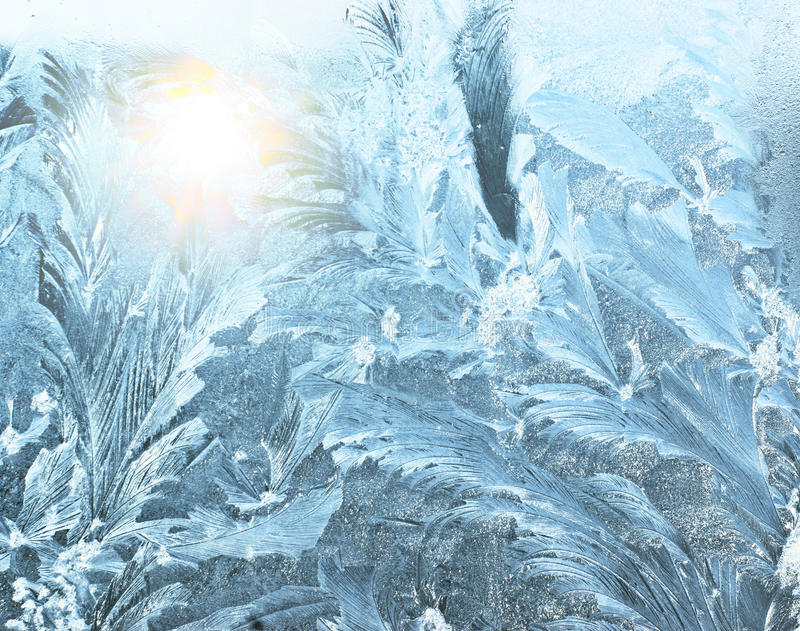 Frosty pattern. And sunlight on a winter window glass royalty free stock image