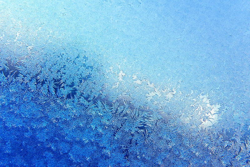 Frosty pattern. Blue formation of snow pattern on closeup window stock photo