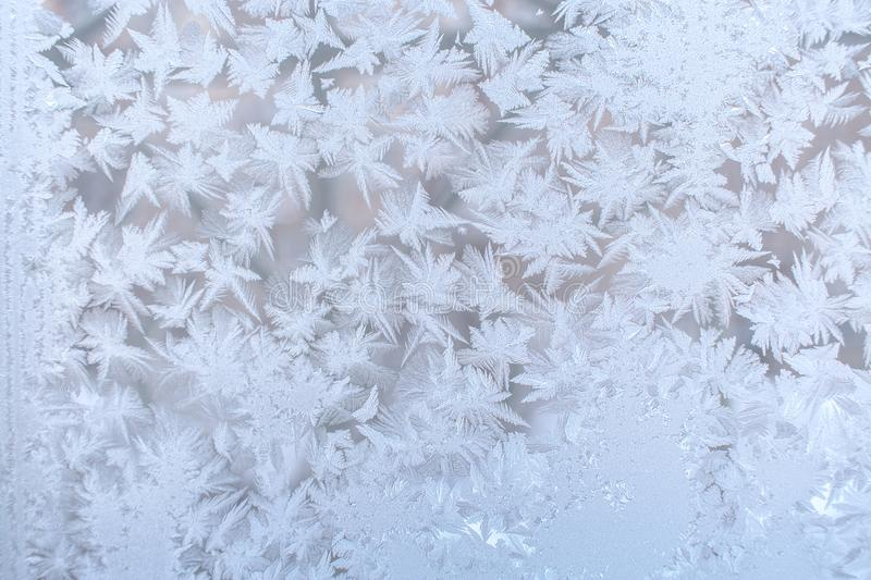 Frosty pattern from many pointed snowflakes on window glass. Selective focus. Christmas background. Beautiful frosty pattern from many pointed snowflakes on royalty free stock photos