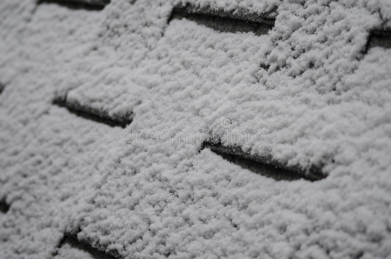 Frosty Snow on shingles of a roof. Snow texture on a shingle of a house roof royalty free stock images