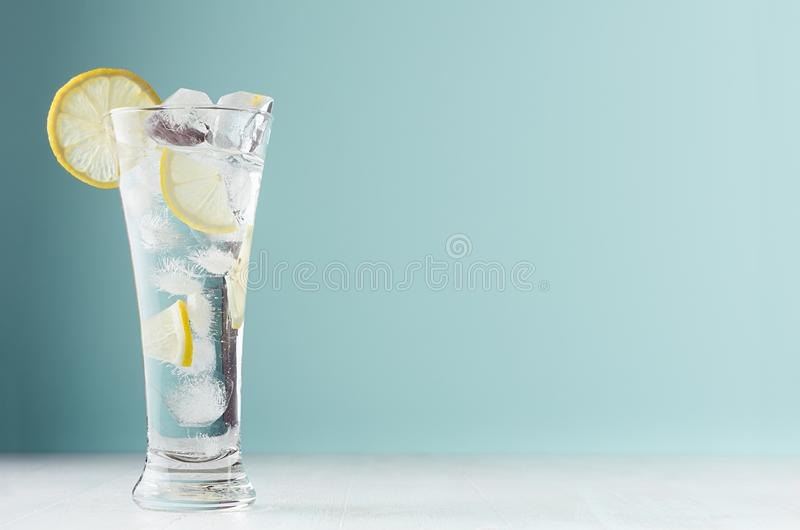 Frosty transparent lemonade with lemon slices, ice cubes and mineral water in elegant glass on white wood table, mint color wall. Frosty transparent lemonade royalty free stock images