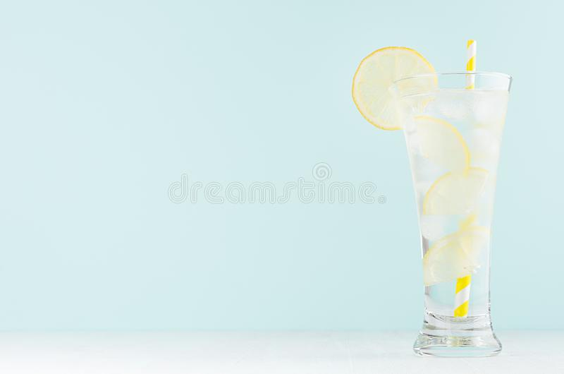 Frosty transparent lemonade with lemon slices, ice cubes, mineral water, yellow striped straw in elegant glass on white wood table. Mint color wall royalty free stock photography