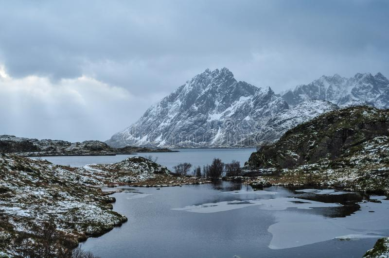 Frosty view on a norwegian fjord with with the sun breaking through the clouds stock image