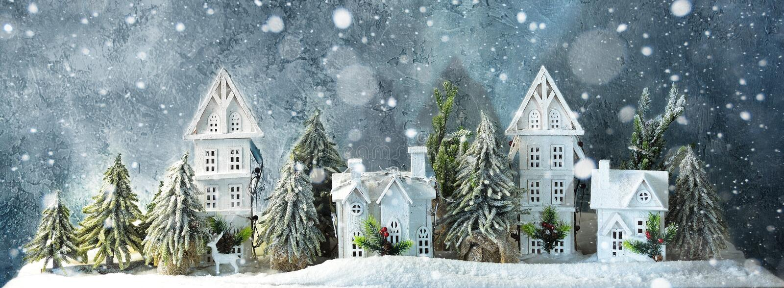 Frosty winter long banner wonderland forest with snowfall, houses and trees. Christmas greetings concept stock images