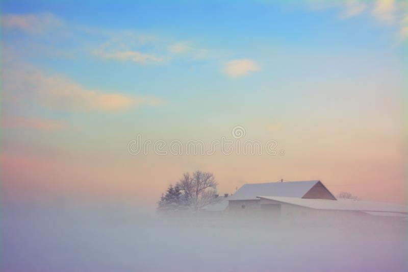 Frosty winter morning, field, house. Sunrise stock photo