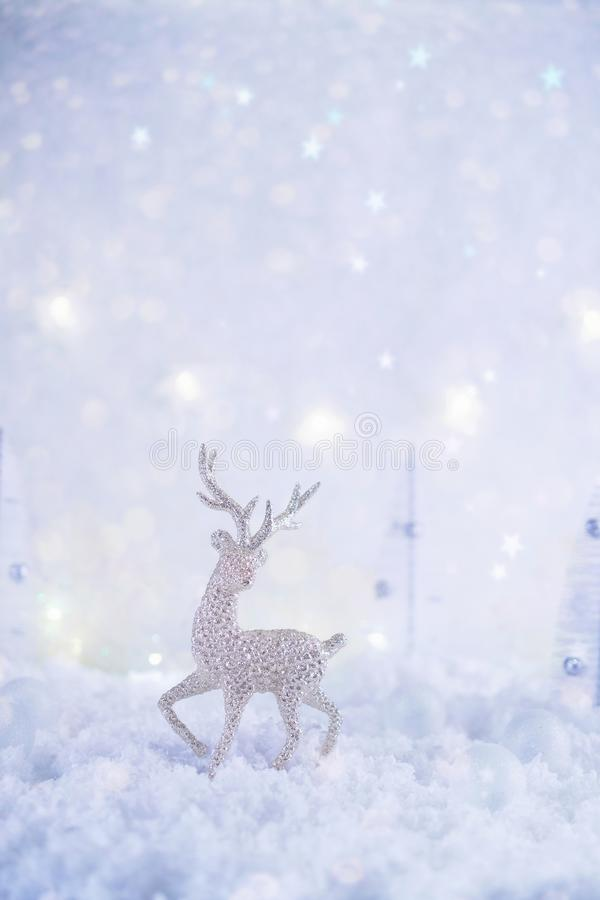 Frosty winter wonderland with toy deer, snowfall and magic lights. Christmas greetings concept royalty free stock photo