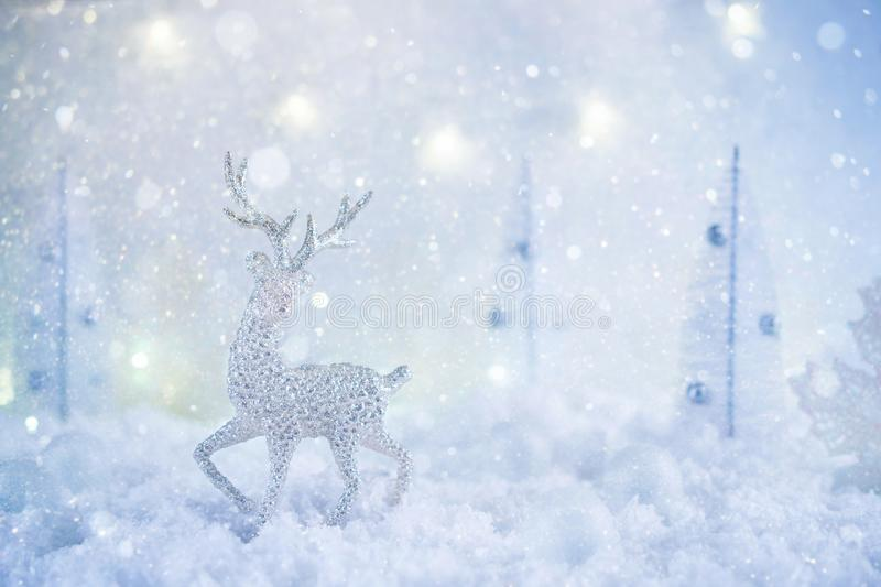 Frosty winter wonderland with toy deer, snowfall and magic lights. Christmas greetings concept stock images