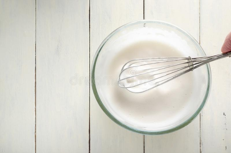 Frothy Aquafaba in Glass Bowl with Whisk From Above on Wood Planked Table. Overhead shot of frothy aquafaba chickpea water. Vegan egg white replacer in glass royalty free stock image