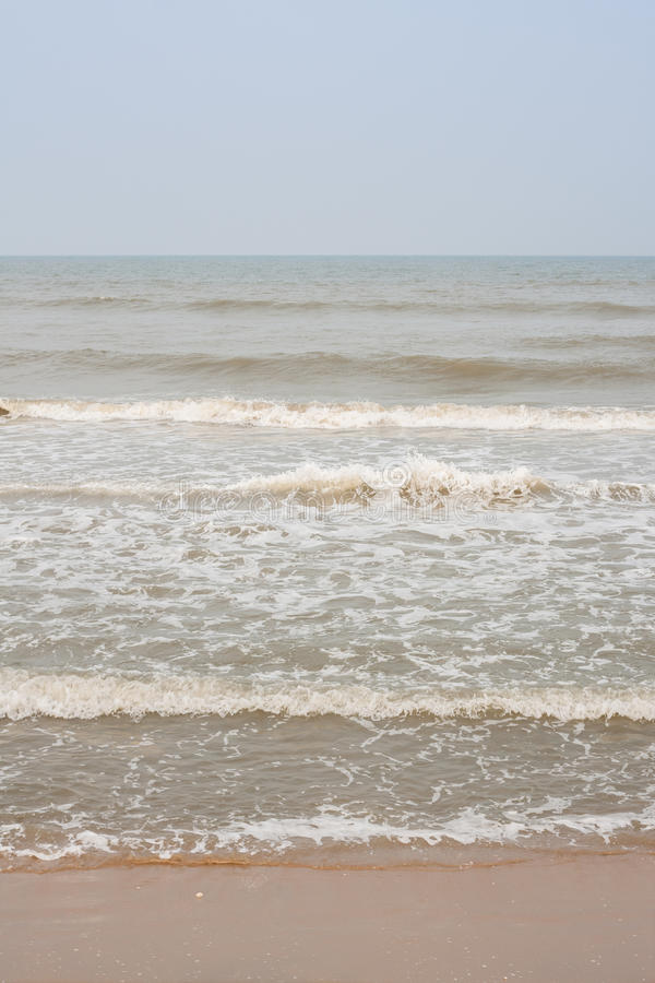 Frothy waves on beach stock image