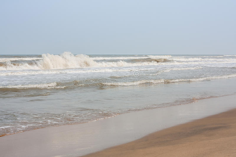Frothy waves on beach stock images