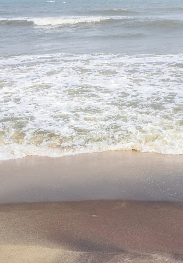 Frothy waves on beach with patterns royalty free stock photography