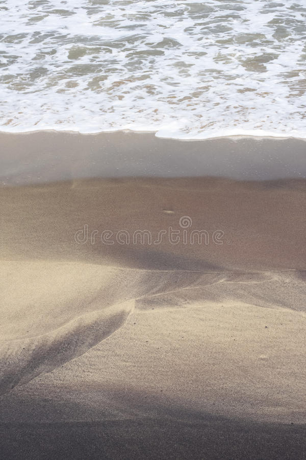 Frothy waves form pattern on beach sand stock images