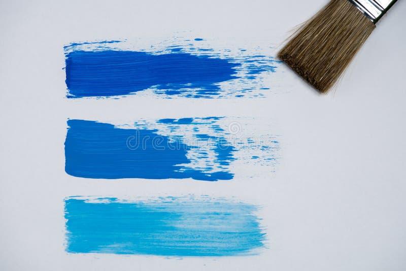 Frotte les nuances bleues de peinture à l'huile sur un fond blanc image libre de droits