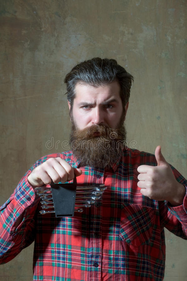 Frown bearded man holding set of wrenches with thumbs up royalty free stock photography